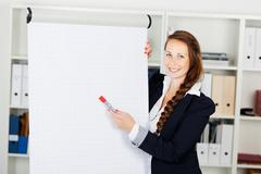 business woman pointing to a blank flip chart - stock photo