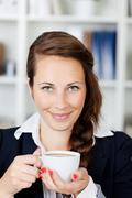 young woman smiling with coffee mug - stock photo