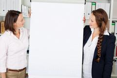 businesswomen giving a flip chart presentation - stock photo