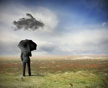 businessman under a black cloud - stock photo