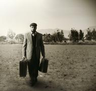 emigrant with the suitcases - stock photo