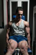 Bodybuilder doing heavy weight exercise for legs on machine leg extensions Stock Photos