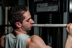 young body builder doing heavy weight exercise for back - stock photo
