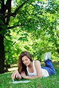 Attractive girl relaxing in park Stock Photos