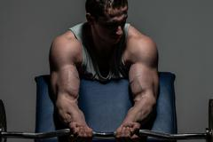 Young bodybuilder doing heavy weight exercise for biceps with barbell Stock Photos