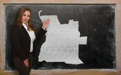 teacher showing map of angola on blackboard - stock photo