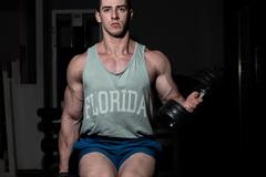 young bodybuilder doing heavy weight exercise for biceps with dumbbell - stock photo