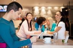 group of girl watching handsome man in cafe - stock photo