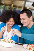 young couple sharing salad - stock photo
