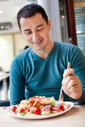 man eating large portion of salad - stock photo