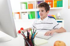 smiling boy using computer - stock photo
