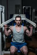 young bodybuilder doing shoulder press on machine - stock photo