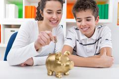 siblings with piggybank - stock photo