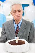 senior man with birthday cake - stock photo