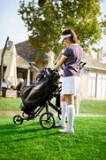 woman arranging your golf equipment - stock photo