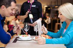 nice dinner in a restaurant - waiter offers wine - stock photo