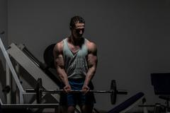 young bodybuilder doing heavy weight exercise for biceps with barbell - stock photo