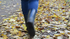 Woman rubber shoes walk toward park path autumn colorful leaves Stock Footage
