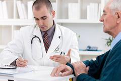 Doctor talking to senior patient Stock Photos
