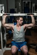Young bodybuilder doing shoulder press on machine Stock Photos