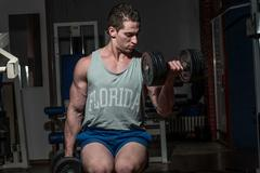 Stock Photo of young bodybuilder doing heavy weight exercise for biceps with dumbbell
