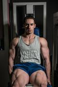 bodybuilder doing heavy weight exercise for legs on machine leg extensions - stock photo