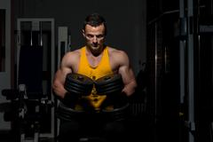 Fitness trainer posing with dumbbells Stock Photos