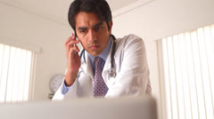 Mexican doctor talking on the phone - stock footage