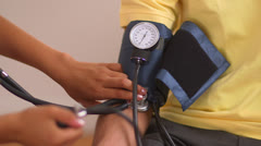 Mexican patient having his blood pressure checked by nurse - stock footage