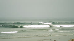 Surfers in distance, riding waves at beach Stock Footage