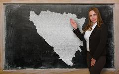 teacher showing map of bosnia herzegovina on blackboard - stock photo