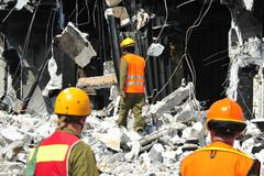 search and rescue through building rubble after a disaster - stock photo