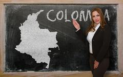 teacher showing map of colombia on blackboard - stock photo