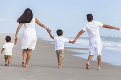 mother, father & two boy children family walking on beach - stock photo