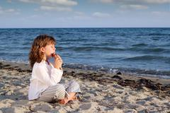 little girl play pan pipe on beach - stock photo