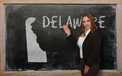 teacher showing map of delaware on blackboard - stock photo