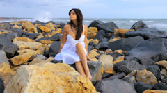 Beautiful female model posing on rocks with wind blowing in her hair Stock Footage