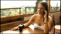 Pretty girl talking on the phone in  italian cafe Stock Footage