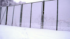 High outdoor tennis court fence covered dense snow winter Stock Footage