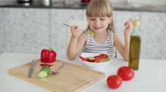 Cute little girl sitting at kitchen table eating vegetable salad and smiling  - stock footage