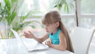 Stock Video Footage of Beautiful little girl sitting at table using laptop and smiling at camera
