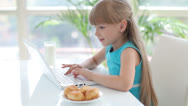 Stock Video Footage of Cute smiling little girl sitting at table using laptop and looking at camera.