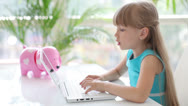 Stock Video Footage of Cute little girl sitting at table with laptop smiling and laughing at camera.