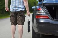 Stock Photo of Man with jack near car on the road