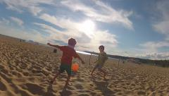 Brothers play with a beach ball Stock Footage