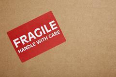 """fragile"" sticker on brown box Stock Photos"