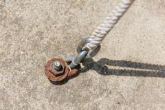 chain fastened with cement and rope - stock photo
