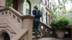 Man walks up brownstone stoop Stock Footage