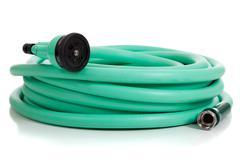 green garden hose with sprayer - stock photo
