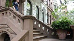 Man descends brownstone stoop Stock Footage